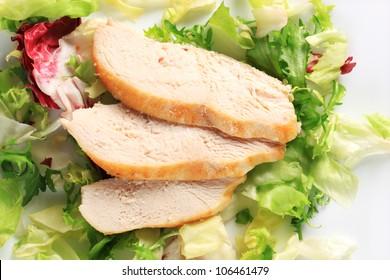 Sliced chicken breast fillet on a nest of green salad