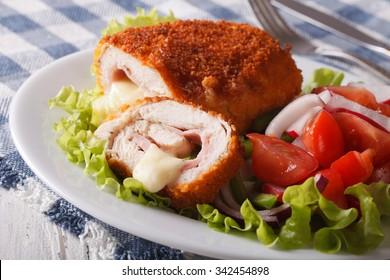 Sliced Chicken cordon bleu and a salad on a plate close-up. horizontal
