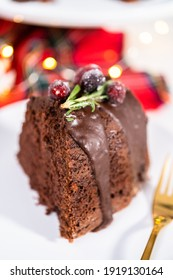 Sliced chocolate bundt cake with chocolate frosting decorated with fresh cranberries and rosemary covered in a white sugar.