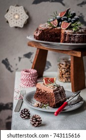 Sliced Chocolate Christmas Cake Decorated with Figs, Grapes, Walnuts and Rosemary