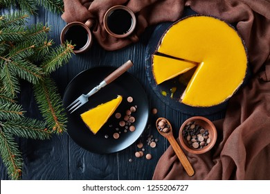 sliced chocolate mango cheesecake. a piece of a cheesecake served on a black plate with dessert fork and chocolate chips. fir tree and cups with coffee on a wooden table, view from above, flatlay