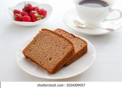 Sliced chocolate pound cake with fresh strawberry and black coffee.