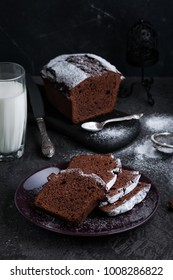 Sliced Chocolate Pound Cake, served with glass of milk on dark background.
