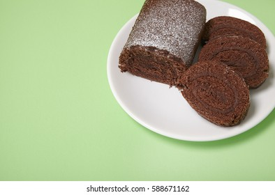 A sliced chocolate Swiss roll cake on a pastel green background with empty space at side