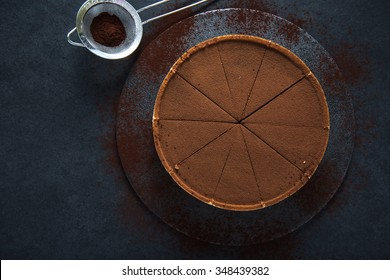 Sliced chocolate tort on dark background, overhead view
