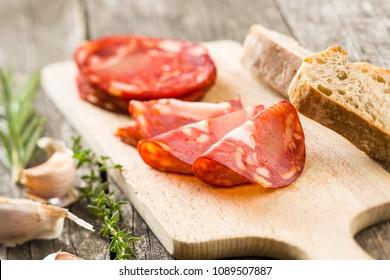 Sliced chorizo salami sausage on cutting board.