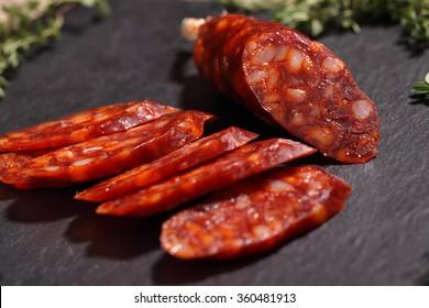 Sliced chorizo sausage on a slate cutting board, Low key image