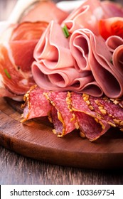 Sliced cold cuts on wooden chopping board