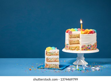 Sliced confetti Birthday cake  with lit candle, colorful icing and Sprinkles over a blue background.
