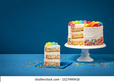 Sliced confetti Birthday cake  with rainbow colored icing and Sprinkles over a blue background.