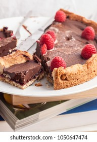 Sliced and crumbled chocolate cake and raspberries on top of a stack of books during the study