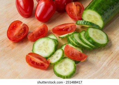 Sliced cucumber and cherry tomatoes - wood background