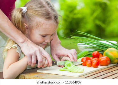 sliced cucumber. Mother teaches daughter  knife cut cucumber