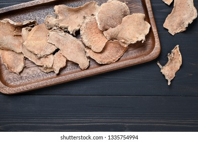 Sliced Curcuma comosa (Wan Chai Mod Luk), an asian traditional herbal remedy on dark wooden background with copy space. Flat lay