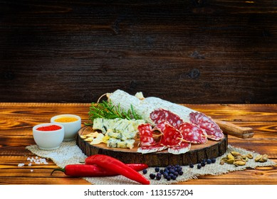 Sliced cured sausage with spices and a sprig of rosemary on dark wooden rustic background.