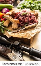 Sliced deer meat prepared for stew of game forest mushrooms herbs vegetables knife and hunter gun.