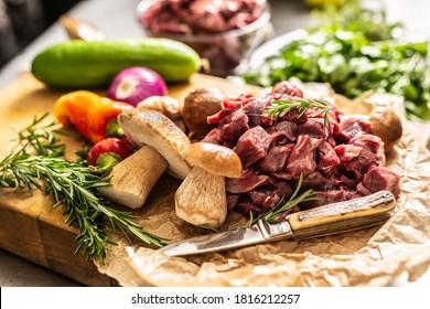 Sliced deer meat prepared for stew of game forest mushrooms herbs vegetables and knife.