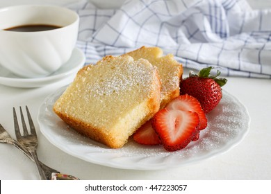Sliced delicious pound cake with fresh strawberries and icing sugar for breakfast served with hot espresso in white cup.