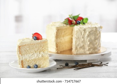 Sliced delicious vanilla cake with fresh berries on wooden table