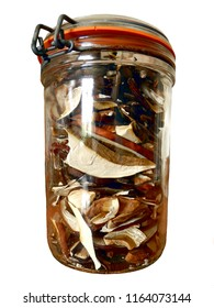 Sliced dried ceps in a sealed glass jar, isolated on a white background