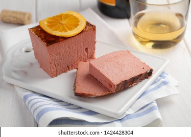 Sliced duck pate topped with slice of orange and a cup of white wine closeup