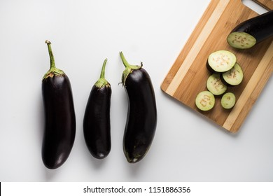 Sliced eggplant on wooden board on white background