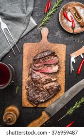 Sliced excellent  medium rare grilled beef barbecue Sirloin steak  on cutting board on rustic kitchen background with knife, spices and glass of red wine. Top view