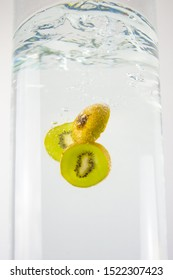 Sliced ​​kiwi falling into the water. Kiwi background in water.
