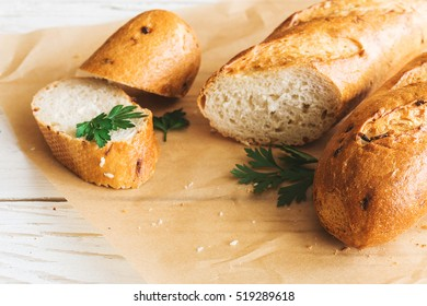Sliced French Baguette on white rustic table. Food background