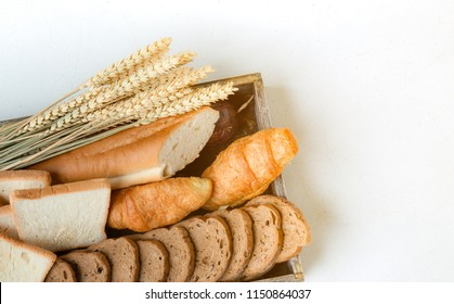 Sliced of french loaf and loaf with croissant on wooden box and ear of rice,Set bread products, pastries,sliced loaf, French baguette,rye bread,wheat branch,cutting bread,croissants,bakery products,