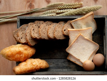 Sliced of french loaf and loaf with croissant on wooden box and ear of rice,Set bread products, pastries,sliced loaf, French baguette,rye bread,wheat branch,cutting bread,croissants,bakery products