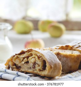 Sliced fresh baked homemade apple strudel over towel on kitchen table with jug of milk and apples. With window as background. Rustic style. Natural day light. Square image with selective focus