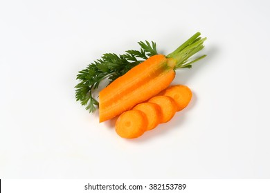 sliced fresh carrots with leaves on white background