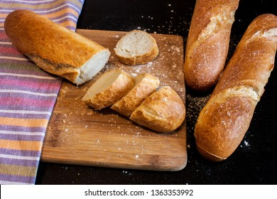 Sliced fresh crusty baguette and two whole baguette on a wooden board against the background of striped towels on a dark table.