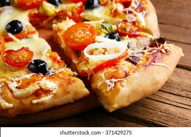 Sliced fresh pizza on wooden table closeup