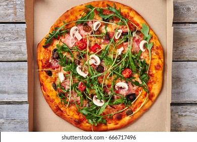 Sliced fresh pizza, wooden background. Appetizing italian pizza on kraft paper.