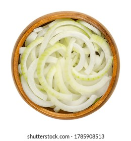 Sliced fresh white onions in wooden bowl. Onions cut into rings. A cultivar of dry onion,  Allium cepa, with white skin and flesh. Closeup, from above, on white background, isolated, macro food photo.