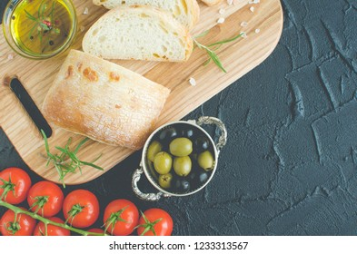 Sliced freshly baked ciabatta bread on wooden cutting board with rosemary, olive oil, tomatoes, olives and salt on dark stone black concrete table. Italian food concept. Top view. Copy space.