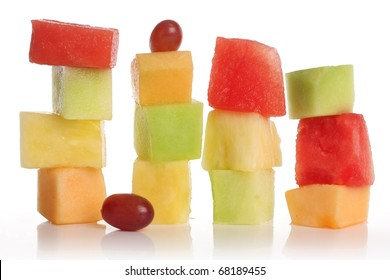 Sliced fruit stacks in watermelon, cantaloupe, pineapple, honeydew and grapes.
