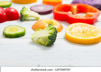 sliced fruit and vegetable circles on white wood table