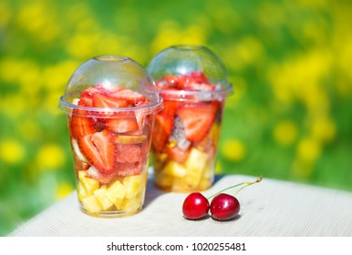 Sliced Fruits arranged in plastic cups