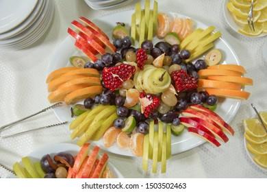 sliced fruits are inside the plate. Mandarin, grape, pomegranate, apple, orange, Acca sellowiana .