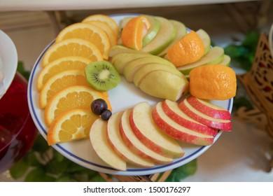 sliced fruits are inside the plate. Red apple, orange, pear, kiwi, grape.