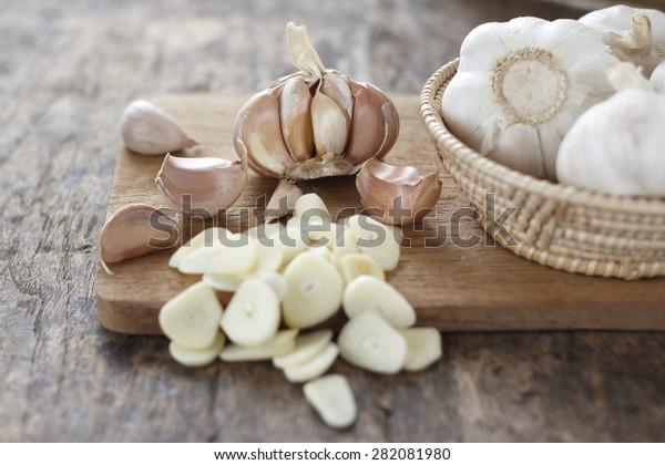 切片大蒜,大蒜丁香,大蒜燈泡柳條籃的地方在老式木製背景上斬塊