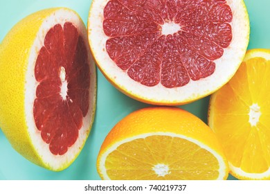 Sliced grapefruits with oranges on the turquoise background