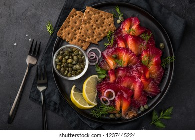 sliced Gravlax,  scandinavian beet cured salmon  served with red onion, capers,  lemon and crisp bread on black plate,  top view