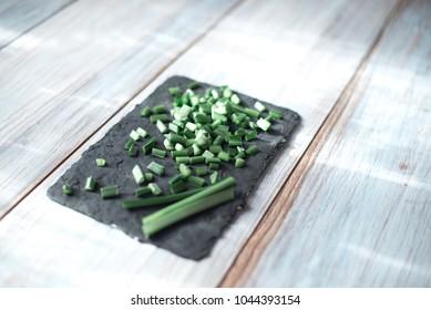 Sliced green stems on a black kitchen board