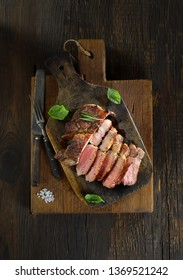 Sliced grilled  barbecue steak   on cutting board on dark wooden background