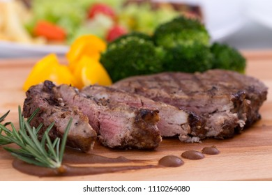 Sliced grilled beef barbecue Striploin steak on wooden cutting board.