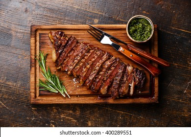 Sliced grilled beef barbecue Striploin steak with chimichurri sauce on cutting board on dark wooden background